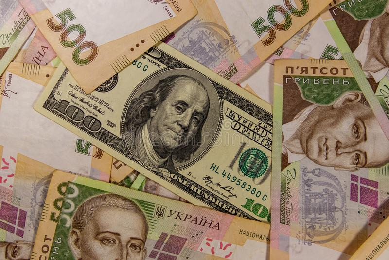 Cem notas de dólar no fundo do ucraniano cinco cem cédulas do hryvnia foto de stock royalty free