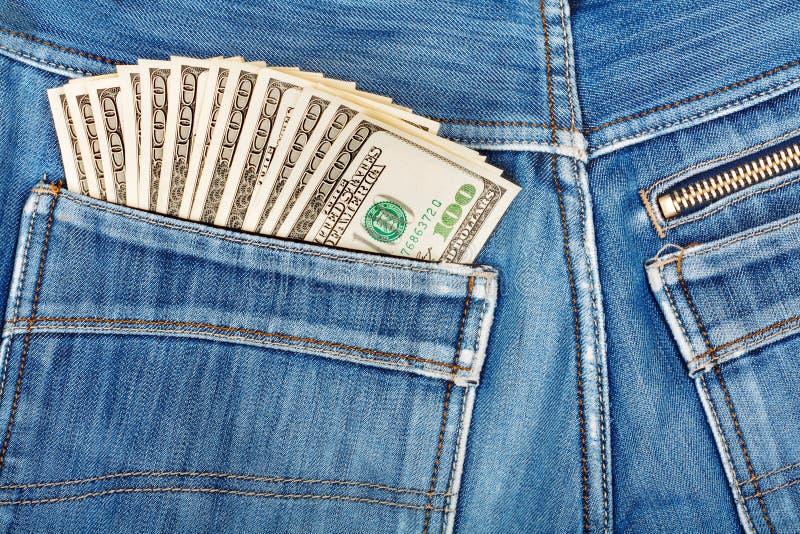 Cem notas de dólar que colam no bolso traseiro da sarja de Nimes foto de stock