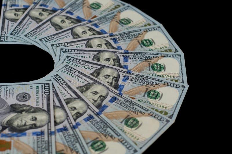 Cem notas de dólar são ventiladas para fora em um fundo preto Vista lateral superior imagem de stock