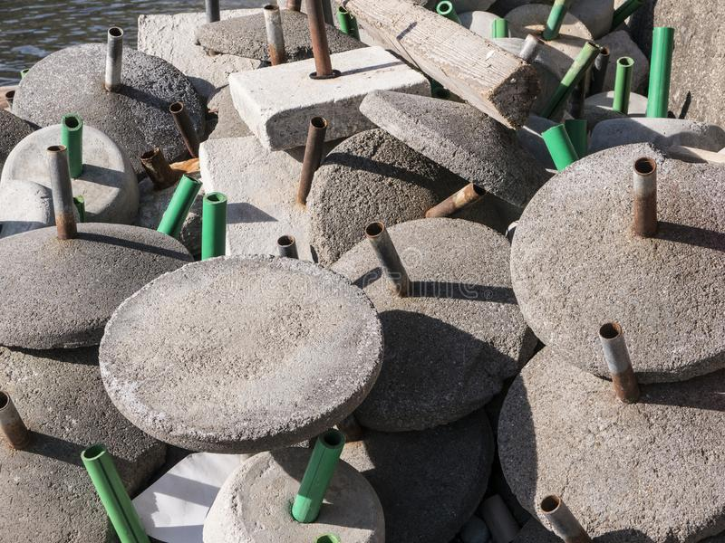 Cement beach sunshade bases dumped in a heap top view stock photography