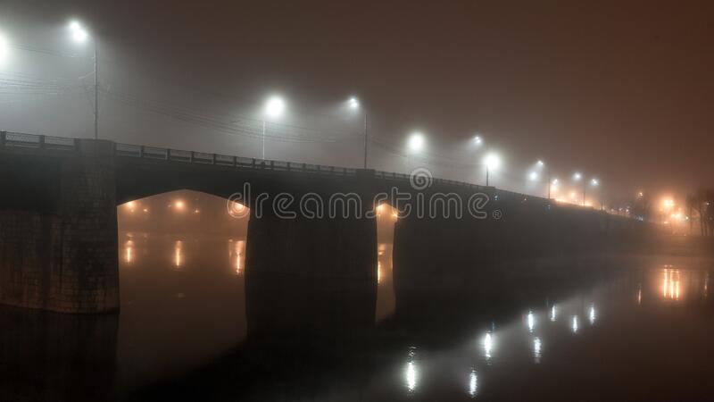 Cement bridge in thick fog. Street lights illuminate road at night, reflecting in calm dark river water. Mystical atmosphere. royalty free stock photos