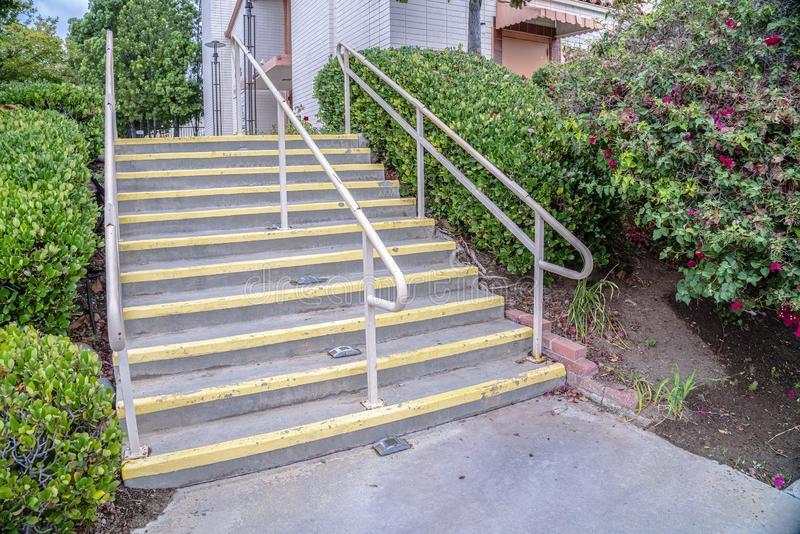 Cement entrance steps with yellow warning on a sunny day. Cement entrance steps with yellow warning painted on the treads viewed from below with hand rails royalty free stock images