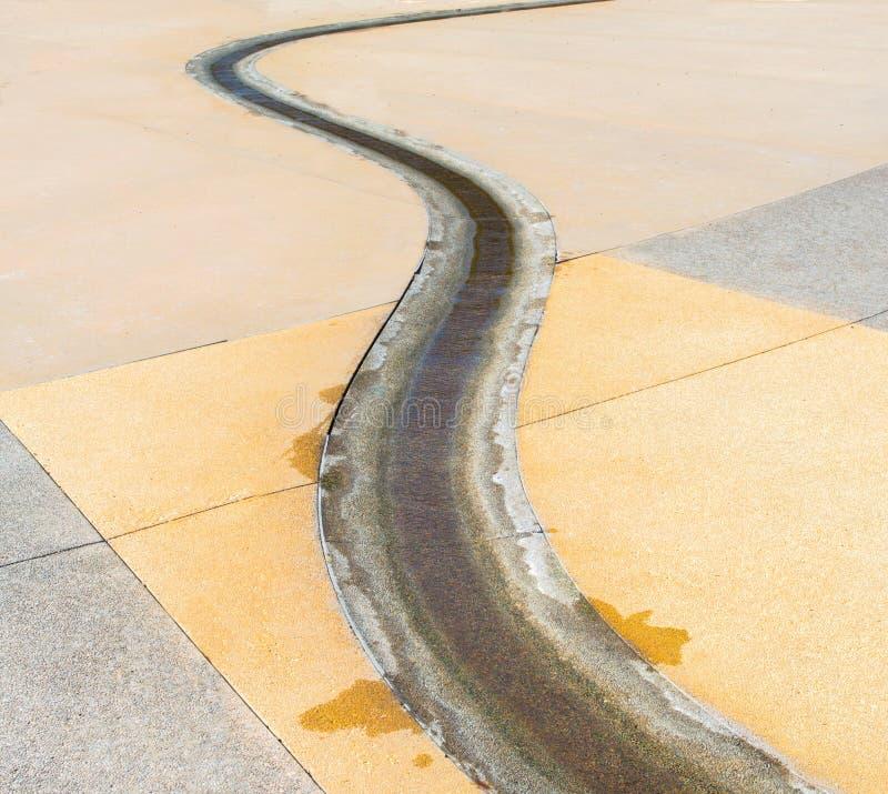 Cement gebogen waterweg met water dat erdoorheen stroomt stock afbeelding