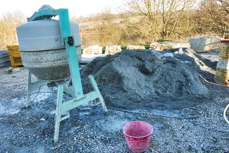 Cement machine close to bunch of gravel with red bucket of water. Cement machine close to bunch of gravel stones with red bucket of water. Construction working stock photo