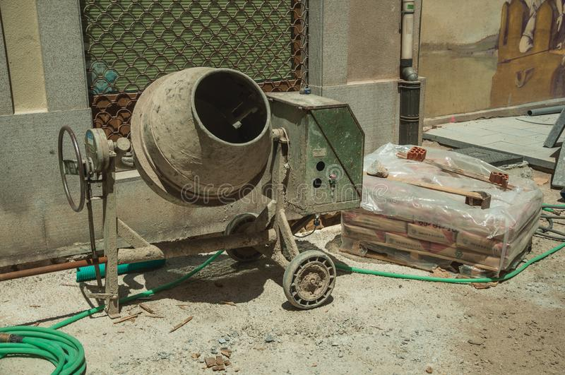 Cement mixer with hose and cement bags in a construction site stock images