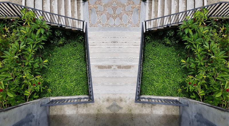 Cement outdoor stairs into the green garden. modern stairway. symmetry staircase photo. outdoor exterior decoration design.  royalty free stock image