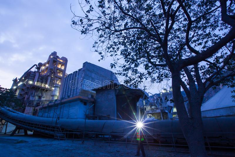 Cement plant factory manufacturing at dusk, sparks of worker with headlamp flashlight during working overtime royalty free stock photography