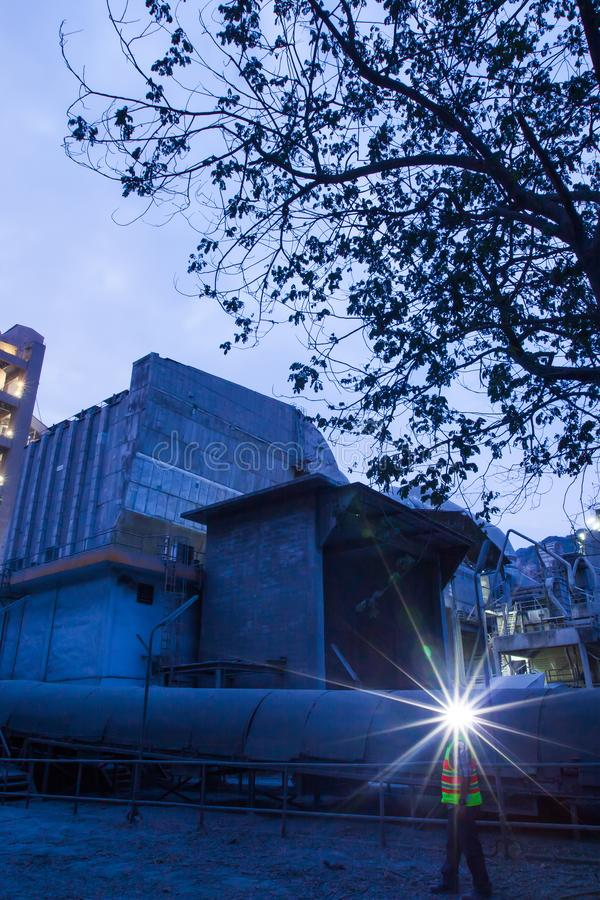 Cement plant factory manufacturing at dusk, sparks of worker with headlamp flashlight during working overtime stock images