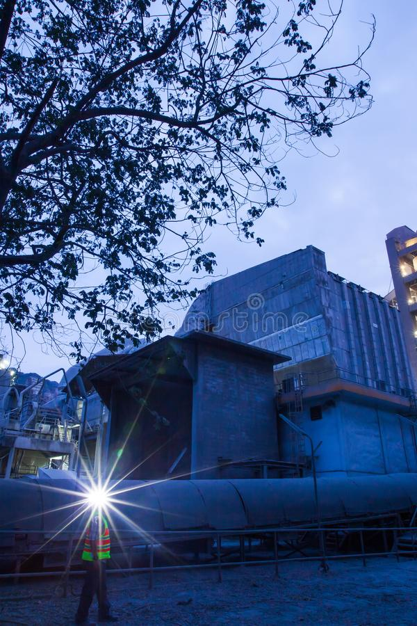 Cement plant factory manufacturing at dusk, sparks of worker with headlamp flashlight during working overtime royalty free stock images