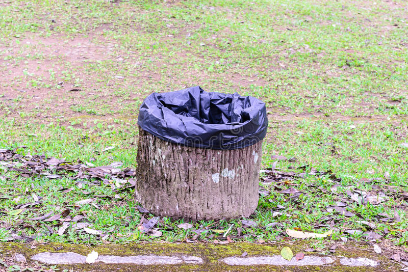 Cement trashcan with black bag at urban garden royalty free stock images