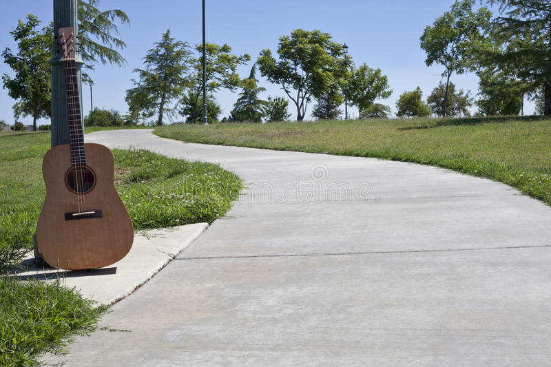 Cement Walkway With Guitar Resting Against a Ligh stock photography