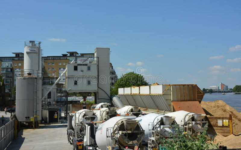 Cement works. Cement mixer trucks wait in line to load up with sand beside the River Thames stock photo