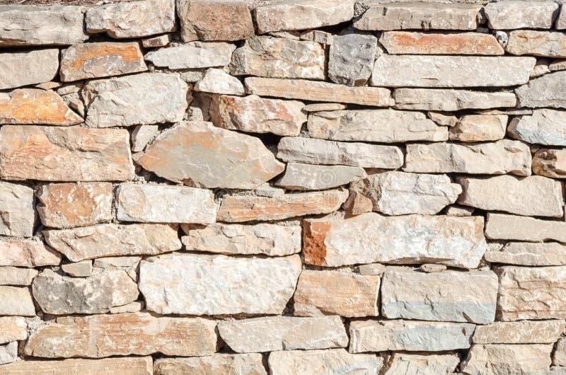 cementitiously被堆积的石头不规则的墙壁  库存图片