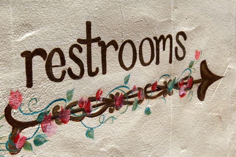 Cementmuur met kleurrijk teken dat `-toilet ` leest stock foto