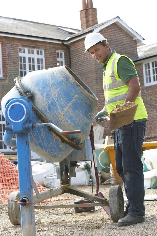 Cemento de mezcla del trabajador de construcción foto de archivo libre de regalías