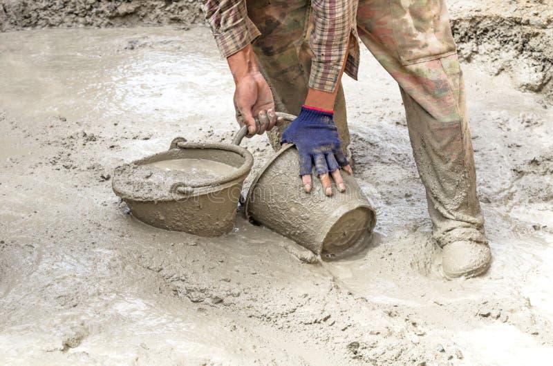 Cemento de mezcla del trabajador de construcción fotos de archivo