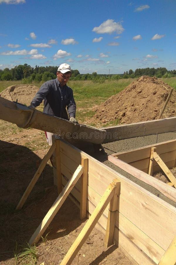 Cemento o calcestruzzo di versamento del muratore della costruzione con il tubo di pompa fotografia stock libera da diritti