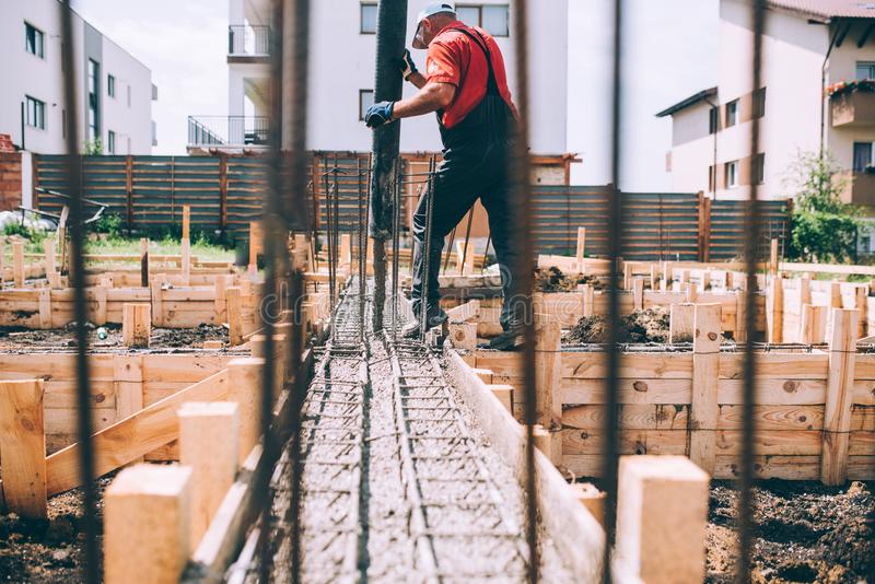 Cemento o calcestruzzo di versamento del muratore della costruzione con il tubo di pompa Dettagli del lavoratore e del macchinari fotografia stock
