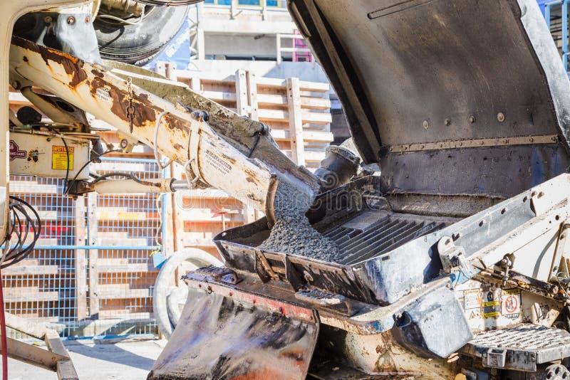 Cemento que es vertido de un camión en un aparato de bombeo fotos de archivo