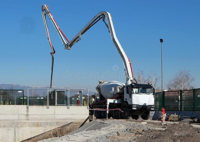 Cementowego melanżeru ciężarówka z swój pompą przygotowywa stawiać beton na podstawie nowy budynek w budowie fotografia royalty free