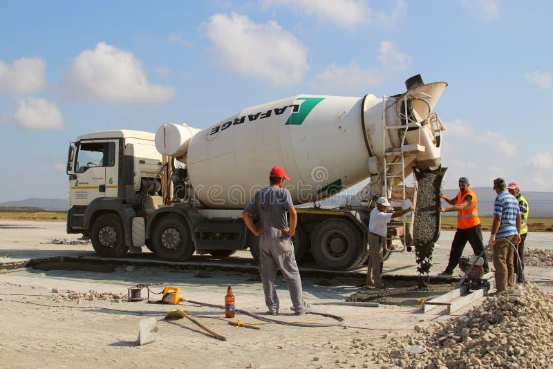 Cementowy ciężarowy dolewanie cement w pas startowy budowę zdjęcie stock