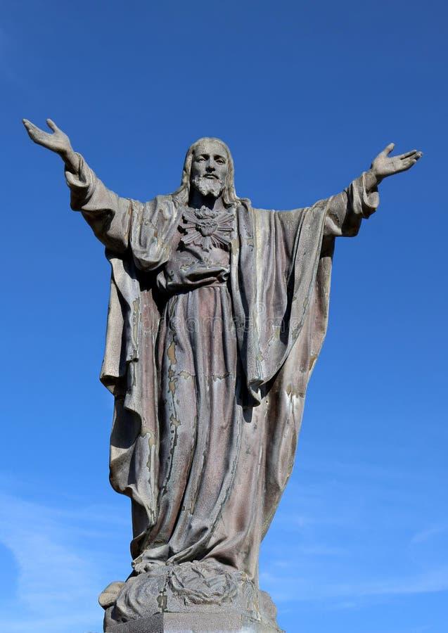 Cementskulptur av Kristus med sakralt hjärtasymbol arkivfoto