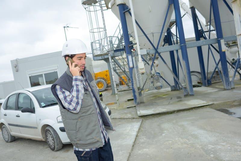 Cementväxtarbetare på telefonen arkivfoton