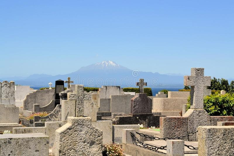 Cemetary with Volcano Calbucco, lake Llanquihue. Cemetary of German immigrants with Volcano Calbuccowith lake Llanquihue seen from Puerto Varas, Patagonia, Chile royalty free stock image