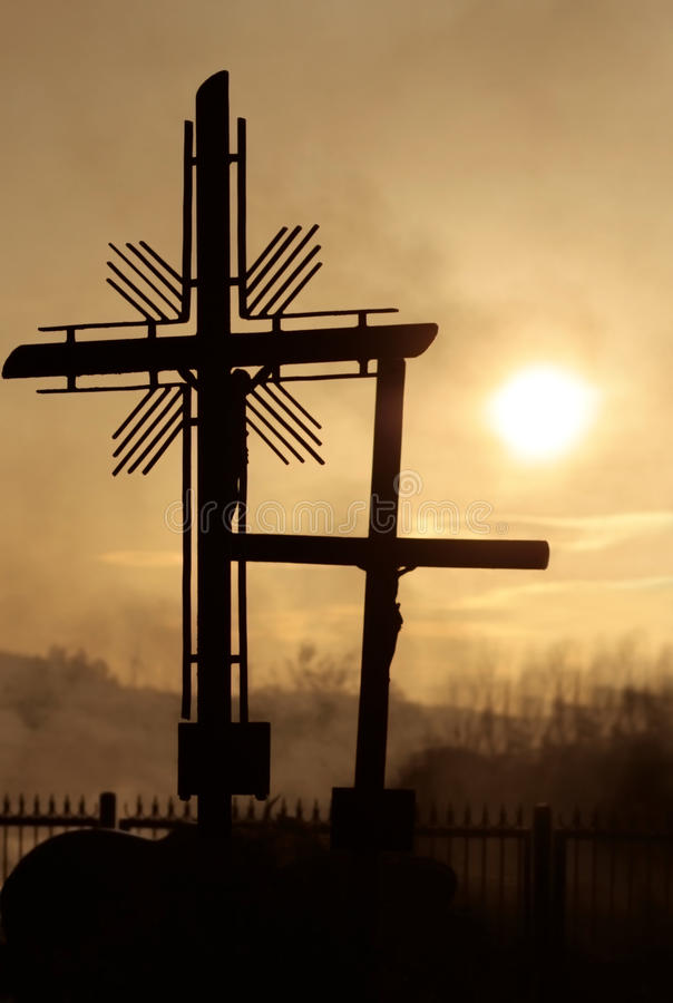 Cemetery. All Saints, cemetery at sunset with cross and silhouetted against sky royalty free stock photo