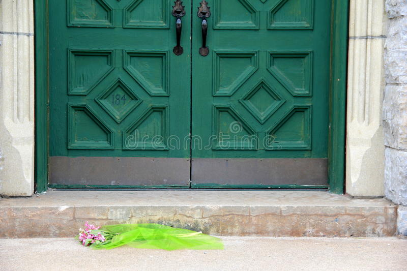 Cemetery crypt with flower bouquet in front of heavy green doors royalty free stock photo