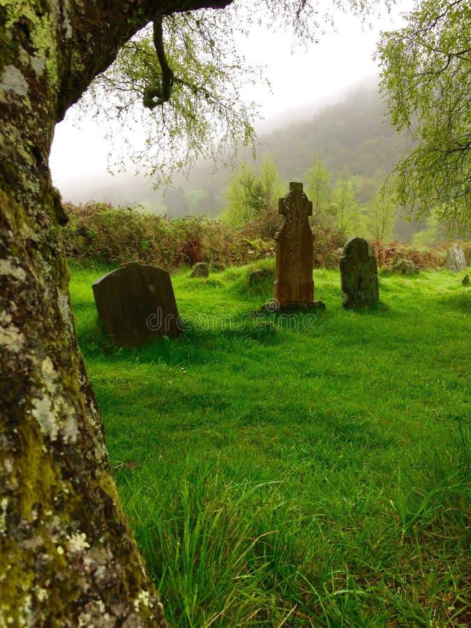 Cemetery, Glendalough Seven Churches, Ireland. Old headstones in green cemetery at Seven Churches in Glendalough, Ireland with foggy skies royalty free stock images