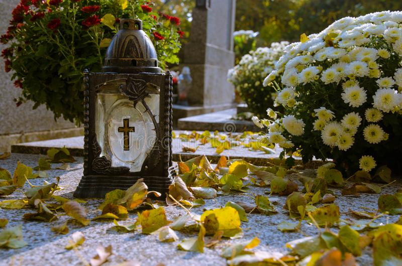 Cemetery lantern with autumn leaves royalty free stock photo