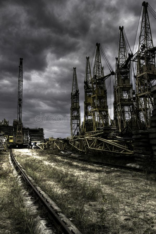 Cemetery of metal lifting cranes with railway tracks and concrete slabs stock photo