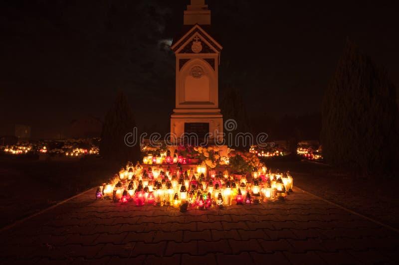 Cemitério - cruz iluminada por luzes da vela imagens de stock royalty free