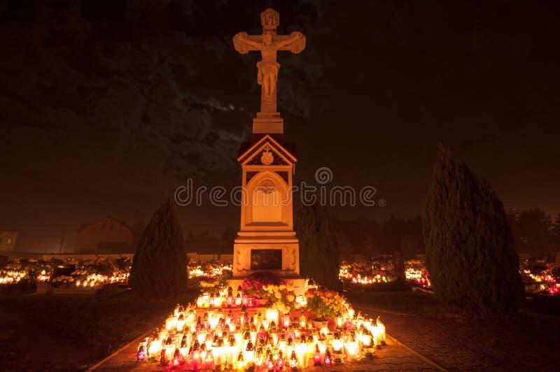Cemitério - cruz iluminada por luzes da vela imagens de stock