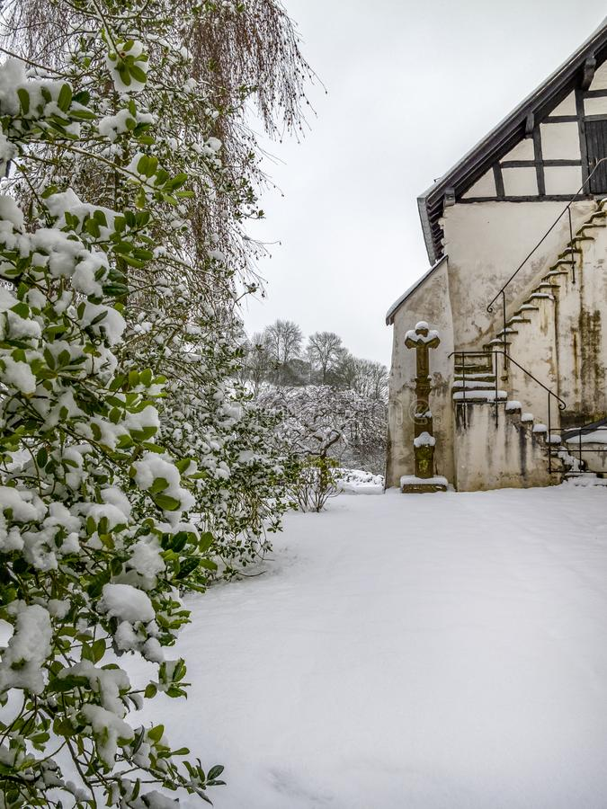 Cemitério nevado de dezembro, em Kronenburg, Reno-Westphalia norte, Alemanha imagem de stock