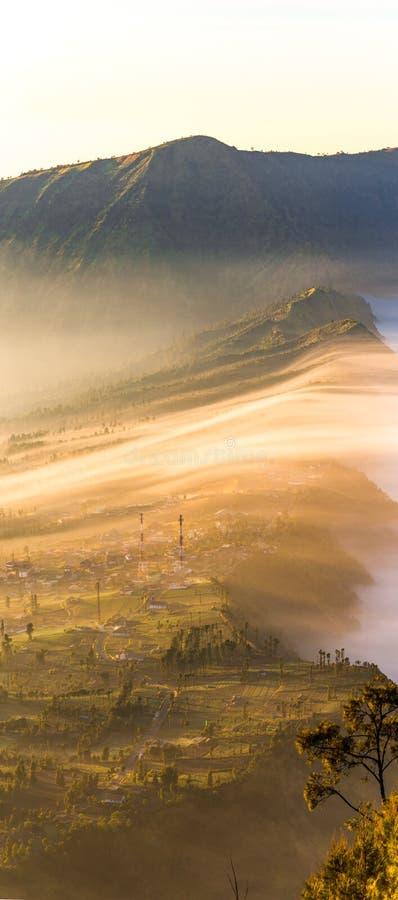 Cemoro Lawang; liten by i morgonmist som placerade på kanten av massiv nord-öst av monteringen Bromo, East Java, Indonesi royaltyfri foto