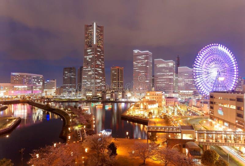 Cenário da noite da área da baía de Minatomirai na cidade de Yokohama, com a torre do marco entre arranha-céus altos da elevação imagens de stock