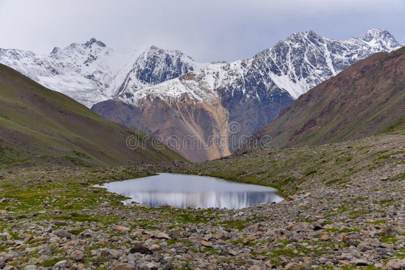 Cenário de montanhas altas nevados com um lago fotos de stock