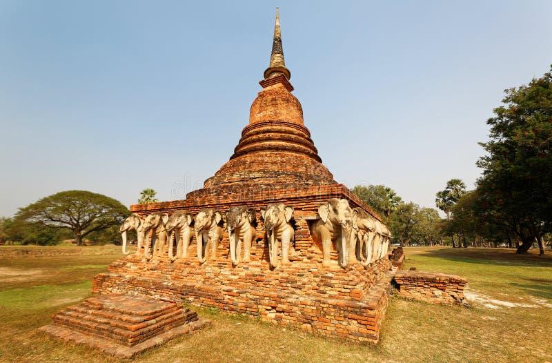 Cenário de Wat Sorasak, um templo budista antigo com as esculturas do elefante que apoiam a base do stupa foto de stock