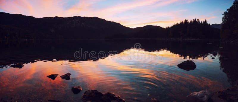 Cenário do pôr do sol de Dreamy no lago eibsee tendo em vista a famosa montanha dos zugspitze foto de stock