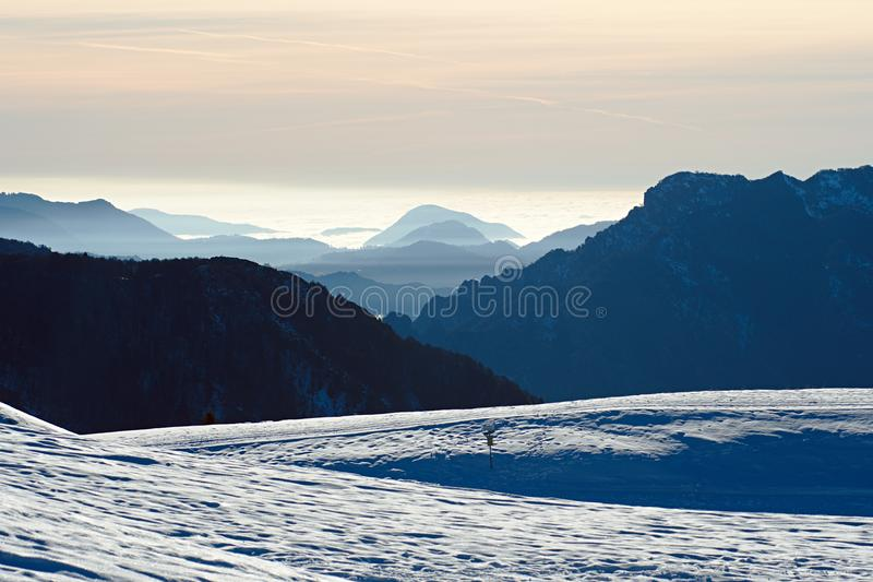 Cenário nevado da montanha em cumes italianos, em um dia ensolarado com a baixa nuvem no fundo imagens de stock