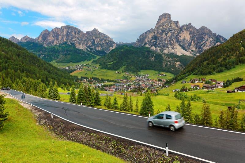 Cen?rio do ver?o de Dolomiti com as vilas no montanh?s gram?neo das montanhas & dos carros ?speros que viajam em uma estrada fotografia de stock