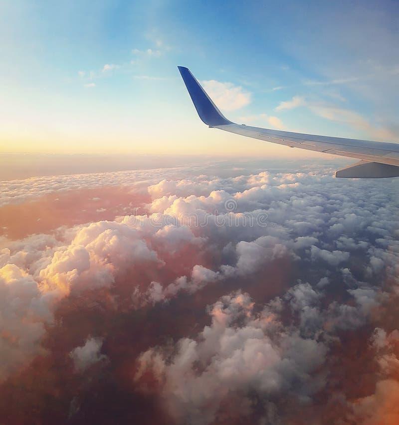 Cena aérea de um voo plano acima das nuvens macias coloridas do por do sol Asa do avião como visto através da janela mosca ao c?u foto de stock royalty free