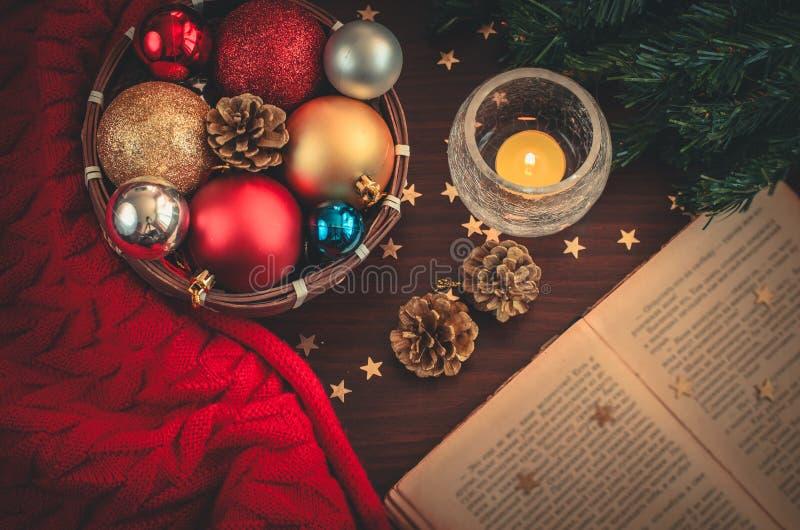 A cena acolhedor bonita com ramo de árvore do xmas, uma cesta pequena com bolas coloridas, uma vela ardente do Natal, abriu o liv fotografia de stock