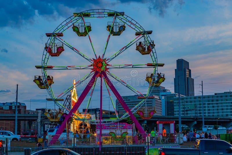 Cena azul da noite da hora do parque de diversões com o beira-rio de Omaha Nebraska da roda de Ferris foto de stock royalty free