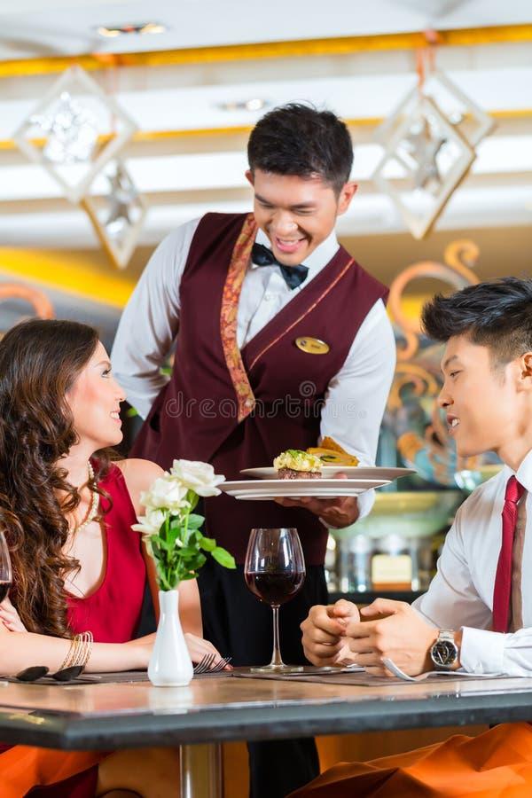 Cena china de la porción del camarero en restaurante u hotel elegante foto de archivo