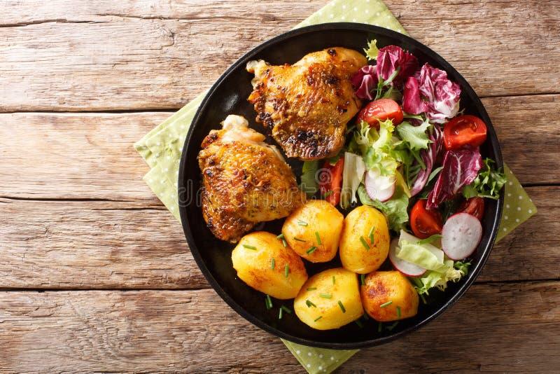 Cena completa de los muslos del pollo con las nuevas patatas y el primer fresco de la ensalada en una placa visi?n superior horiz fotos de archivo