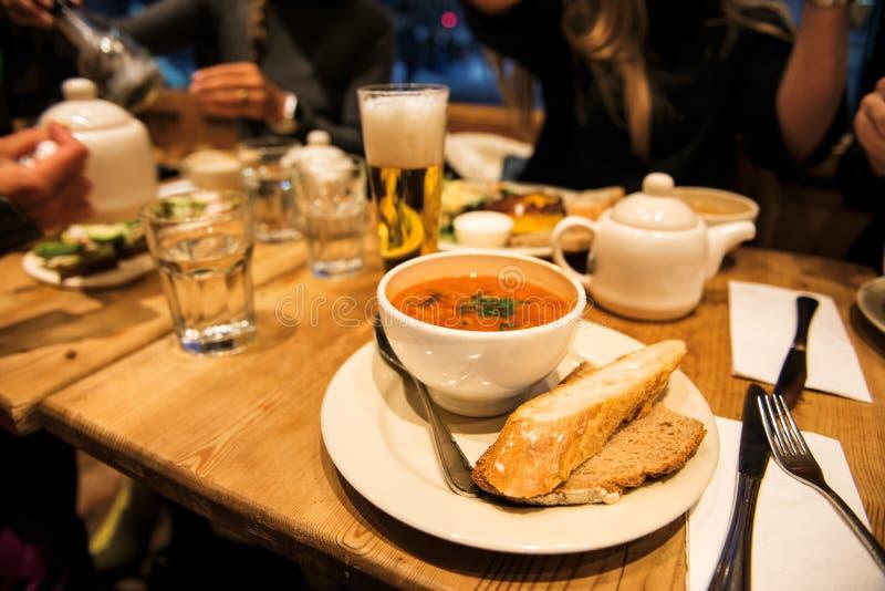 Cena con gli amici nel ristorante con la minestra, il pane, l'insalata e la birra di ministroni immagine stock libera da diritti