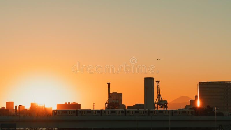 Cena crepuscular bonita do por do sol do Tóquio Opinião da silhueta da cidade, do trem, da indústria, e da montanha de Fuji, espa imagem de stock